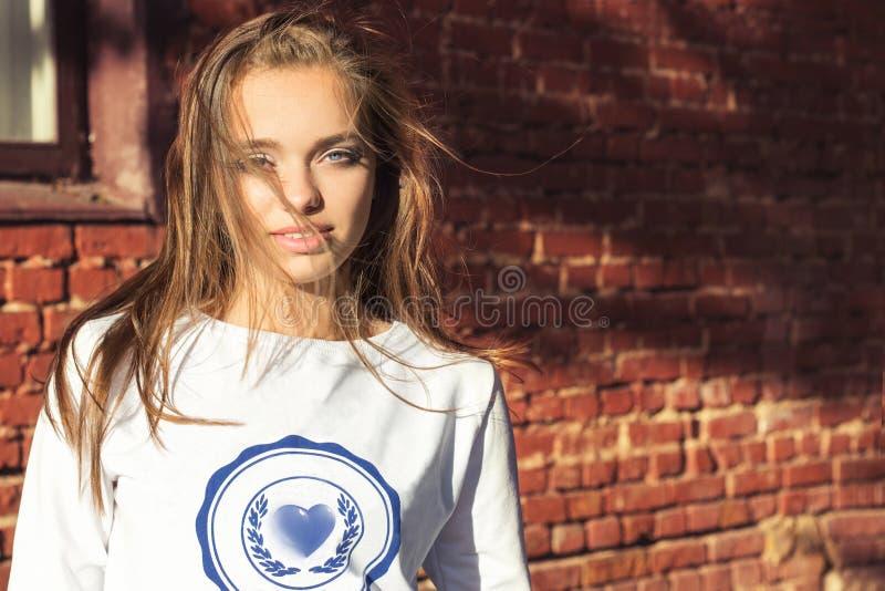 站立在白色夹克风的墙壁附近的美丽的女孩在您的头发吹 免版税库存图片