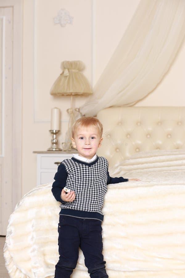 站立在白色床附近的毛线衣的小男孩 免版税库存照片
