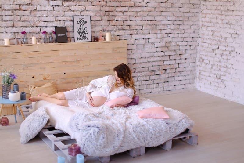 站立在白色礼服、木墙壁和灯的孕妇在背景中 库存照片