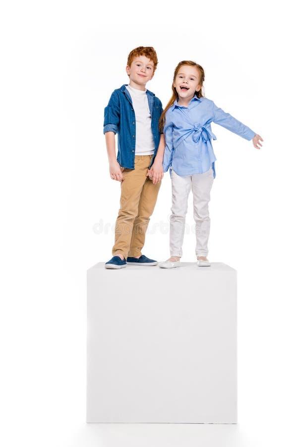 站立在白色立方体和微笑对照相机的逗人喜爱的愉快的孩子 免版税库存照片