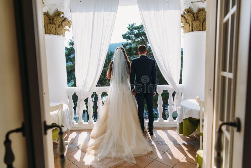 站立在白色阳台和握手,背面图的新婚佳偶 一件美丽的白色礼服的新娘有长的头发的 免版税图库摄影