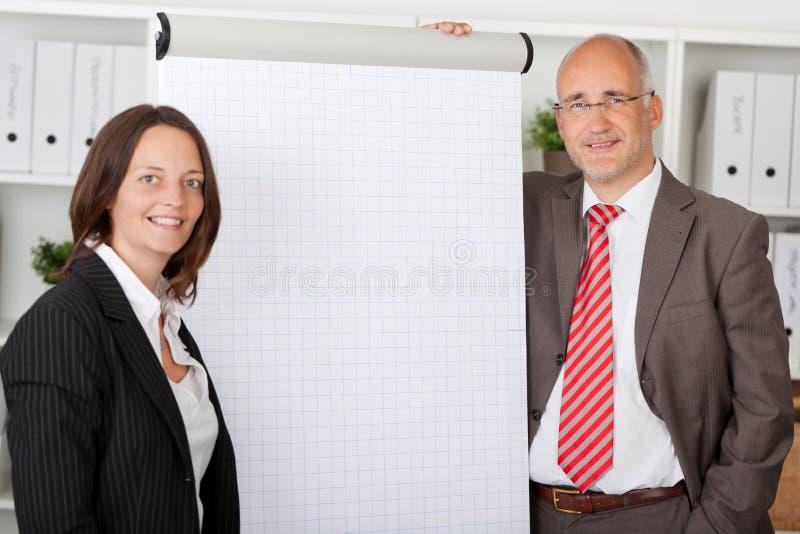 站立在白色flipchart旁边的两个同事 免版税库存图片