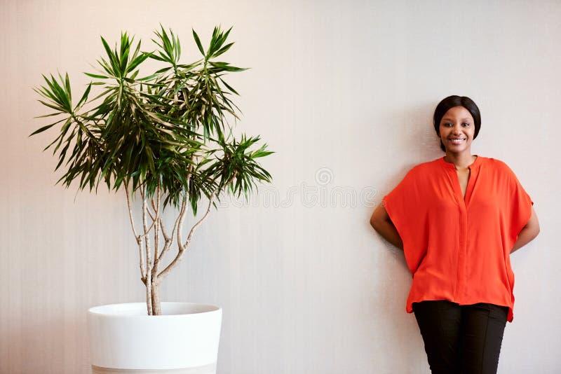 站立在盆栽植物旁边的非洲女实业家微笑对照相机 库存图片