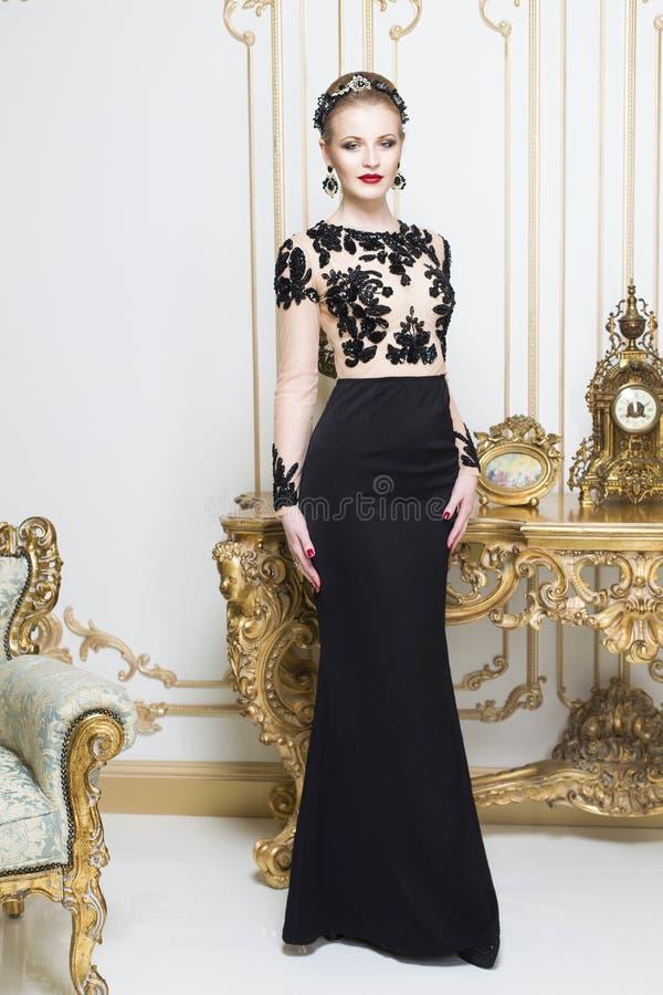 站立在看在照相机的华美的豪华礼服的减速火箭的桌附近的美丽的白肤金发的皇家妇女 库存图片
