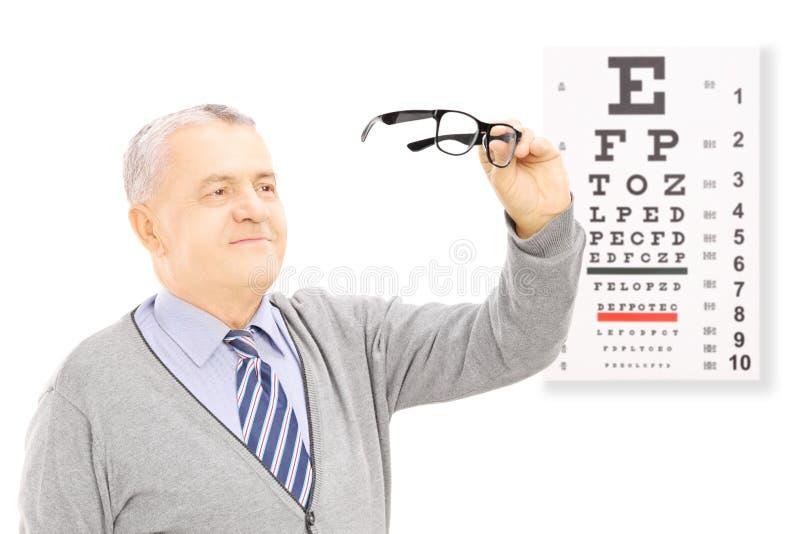 站立在眼力测试前面的资深绅士举行pa 免版税图库摄影