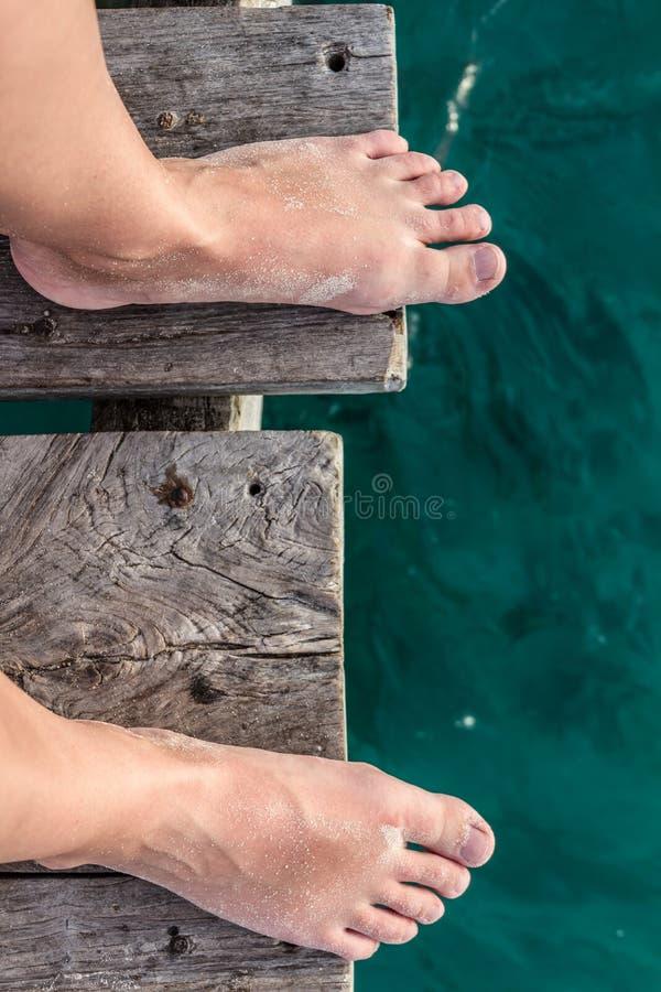 站立在码头和绿松石加勒比海的边缘的妇女脚 免版税库存照片