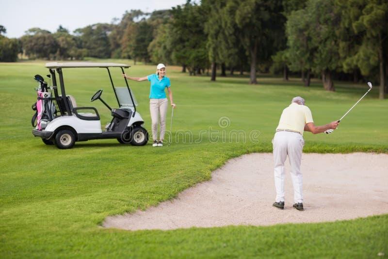 站立在砂槽的成熟高尔夫球运动员在妇女旁边 免版税库存图片