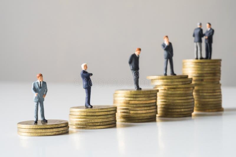 站立在硬币堆的商人 免版税图库摄影