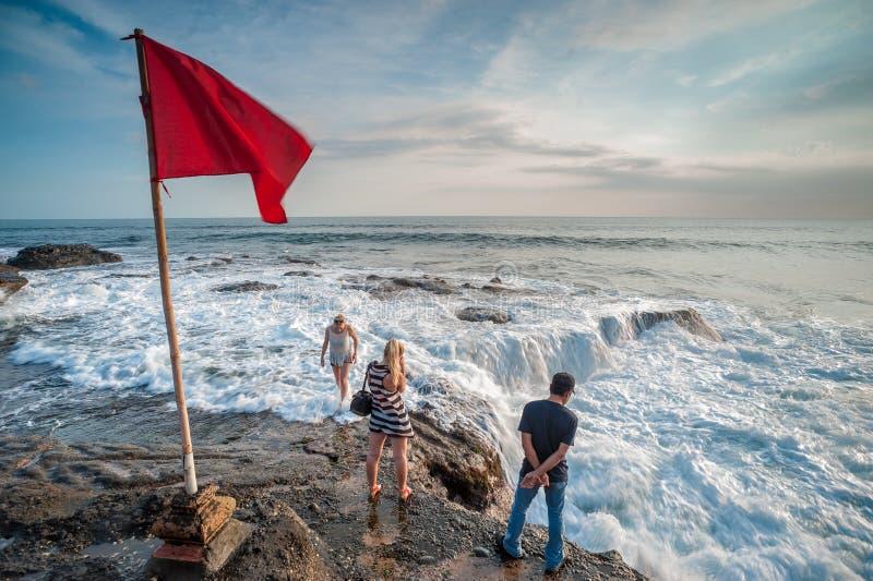 站立在碰撞的波浪的未知的游人 免版税库存图片