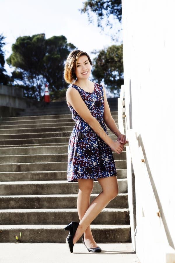 站立在礼服的年轻亚裔美国人妇女户外 免版税图库摄影