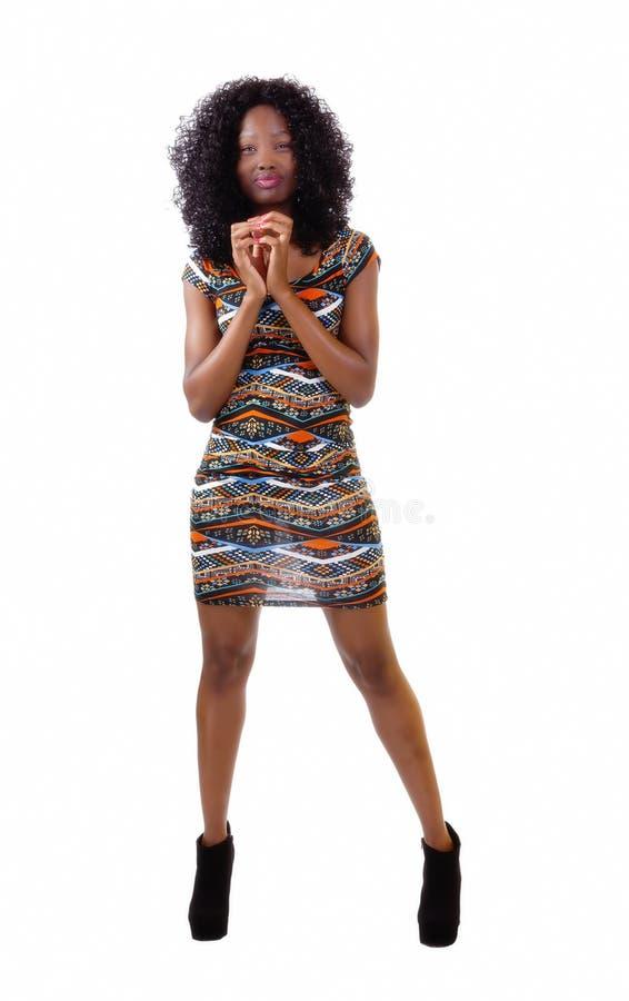 站立在礼服的皮包骨头的非裔美国人的妇女 免版税图库摄影