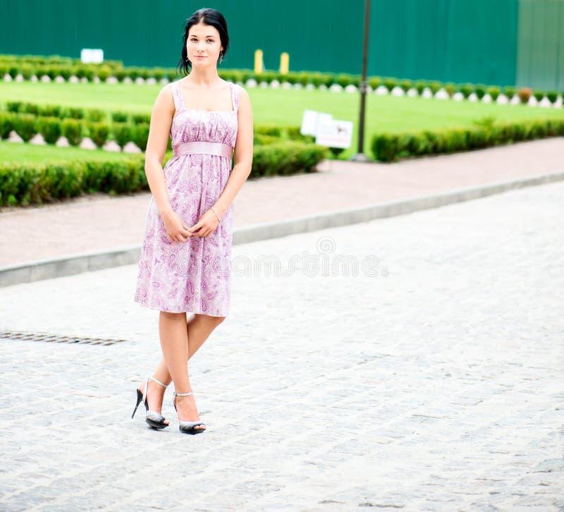 站立在礼服的年轻beautifull妇女 免版税库存照片