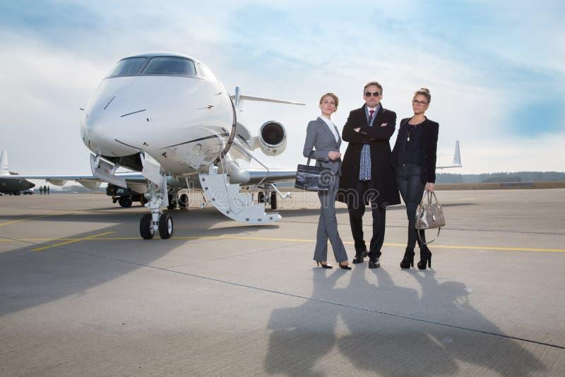 站立在私人喷气式飞机前面的企业队 免版税库存图片