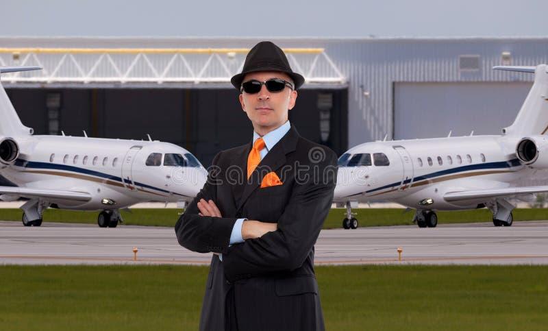 站立在私人喷气式飞机前面的英俊的商人 免版税库存照片