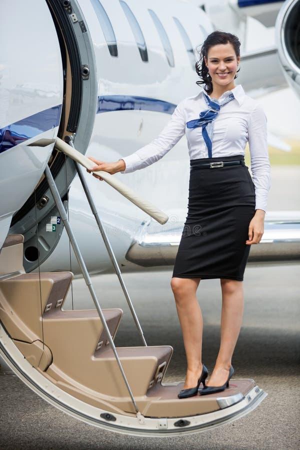 站立在私人喷气式飞机梯子的空中小姐  免版税库存图片