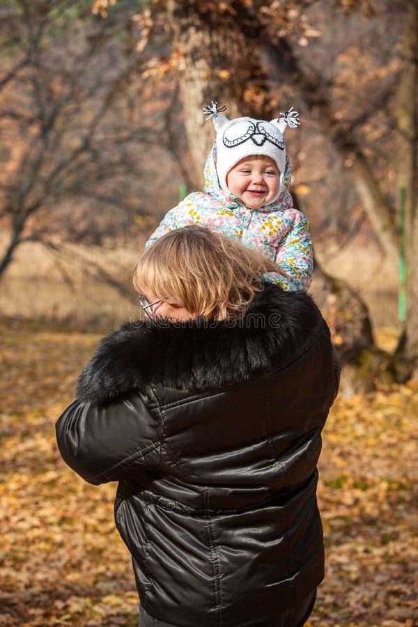 站立在秋叶的小女婴和祖母 免版税库存照片
