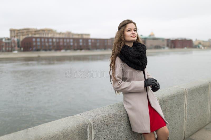站立在秋天的江边的性感的女孩 一件黑外套、一条围巾和一件红色礼服的女孩反对灰色天空 没查出 库存图片
