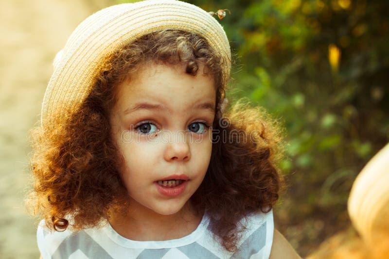 站立在秋天秋天公园的逗人喜爱的可爱的微笑的小卷发的白种人女孩孩子特写镜头画象外面,看i 免版税库存图片