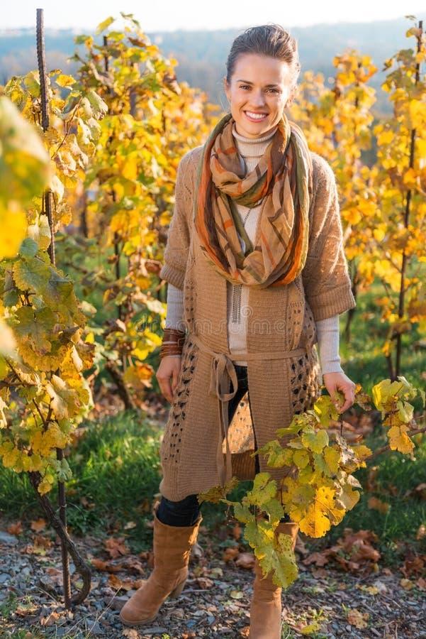 站立在秋天葡萄领域的妇女种葡萄并酿酒的人画象 库存照片