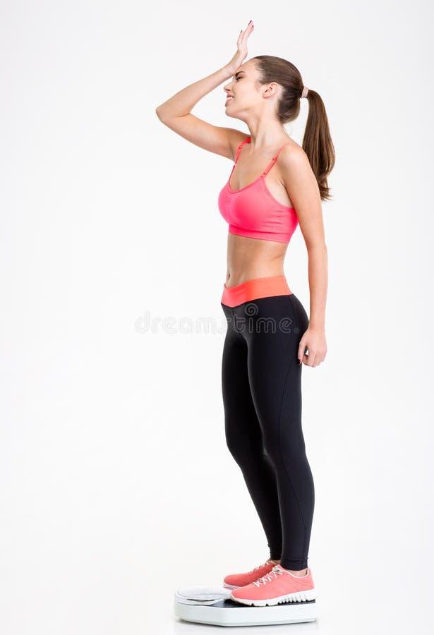 站立在秤的生气失望的健身女孩 库存图片