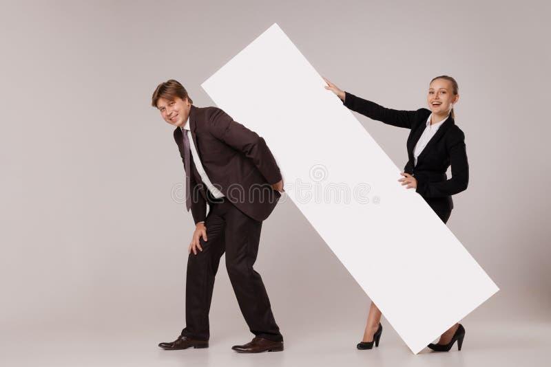 站立在空白的横幅的商人和妇女 免版税库存图片