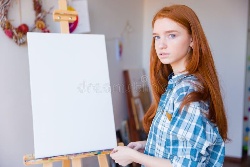 站立在空白的画架附近的美丽的妇女画家在艺术教室 库存照片