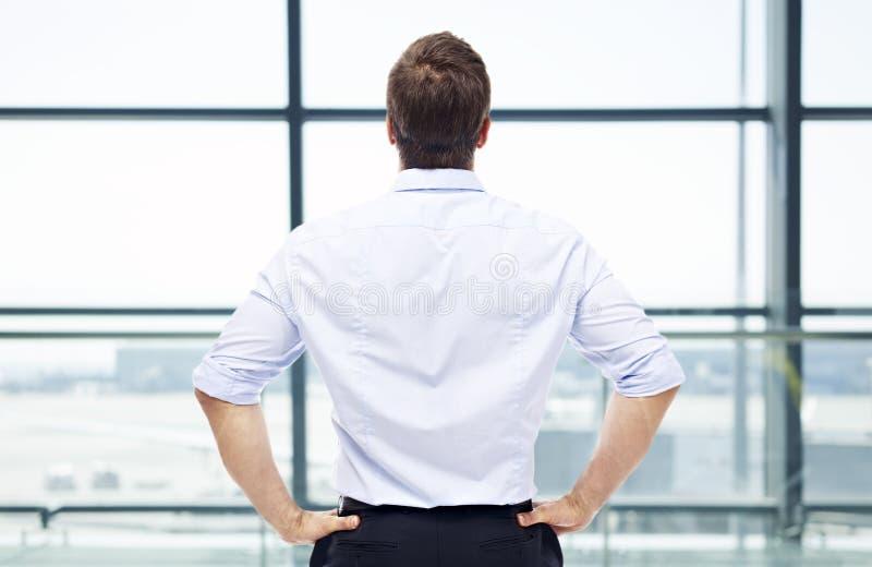站立在窗口前面的人在机场 库存图片