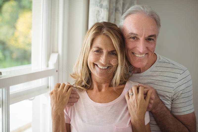 站立在窗口旁边的愉快的资深夫妇画象  库存照片
