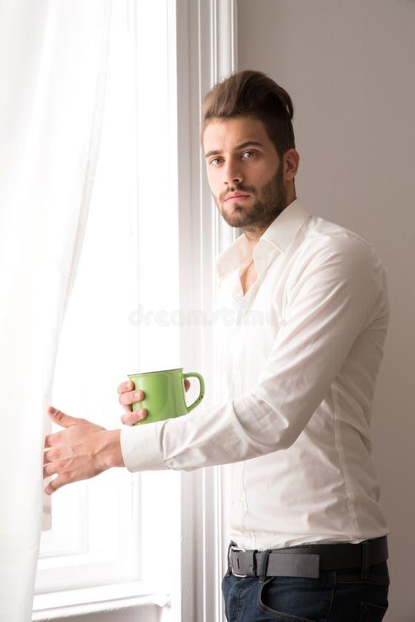 站立在窗口的一个年轻人 库存照片