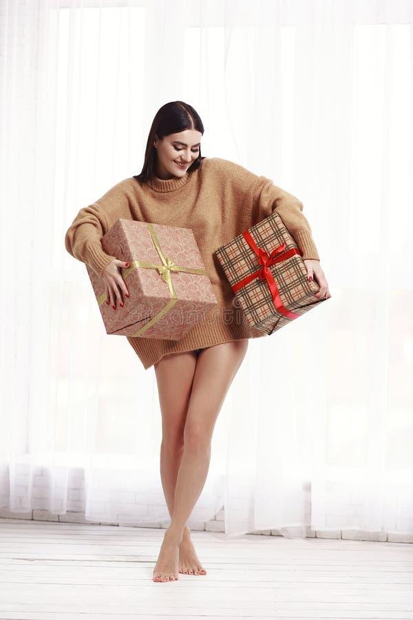 站立在窗口的毛线衣的美丽的女孩 礼物,新年 免版税库存照片