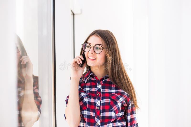 站立在窗口背景的年轻可爱的微笑的白种人女孩,谈话每个手机 库存图片