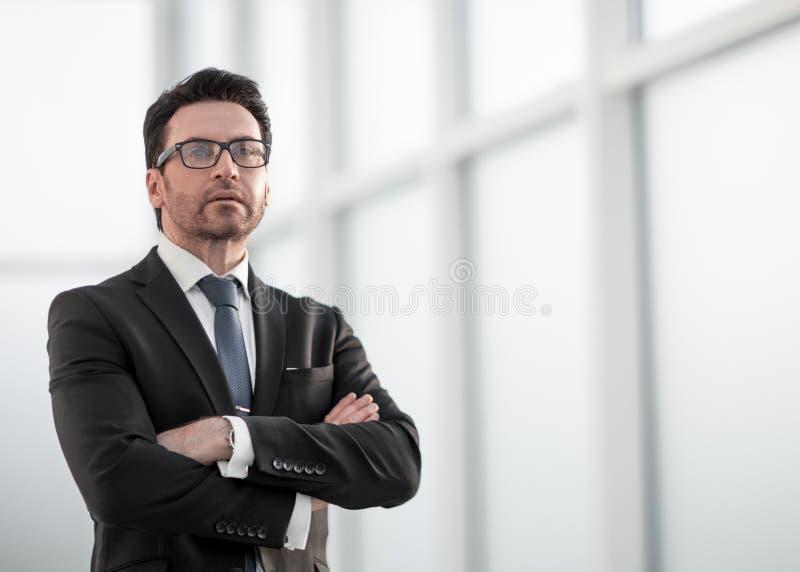 站立在窗口附近和调查它的商人 免版税库存照片