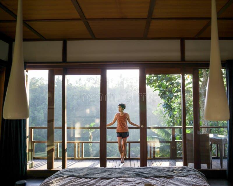 站立在窗口附近的愉快的年轻女人和感觉早晨vibe,看美好的风景在醒在以后 库存图片