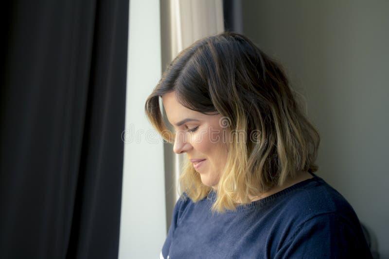 站立在窗口附近的逗人喜爱的可爱的害羞的微笑的少妇 库存图片