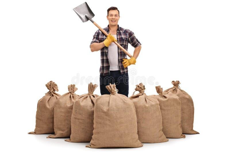 站立在粗麻布大袋后和拿着铁锹的年轻农夫 免版税库存图片