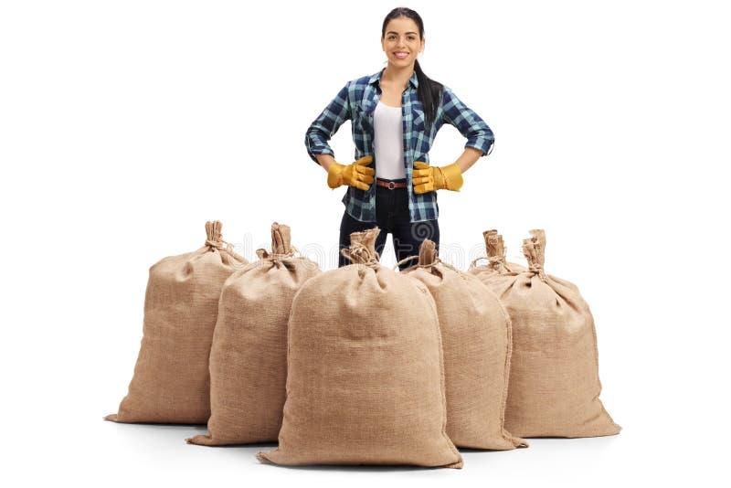 站立在粗麻布大袋后的愉快的女性农夫 免版税库存图片