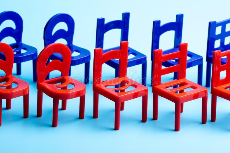 站立在红色和蓝色椅子两行,塑料椅子特写镜头与被雕刻的后面的 免版税库存图片