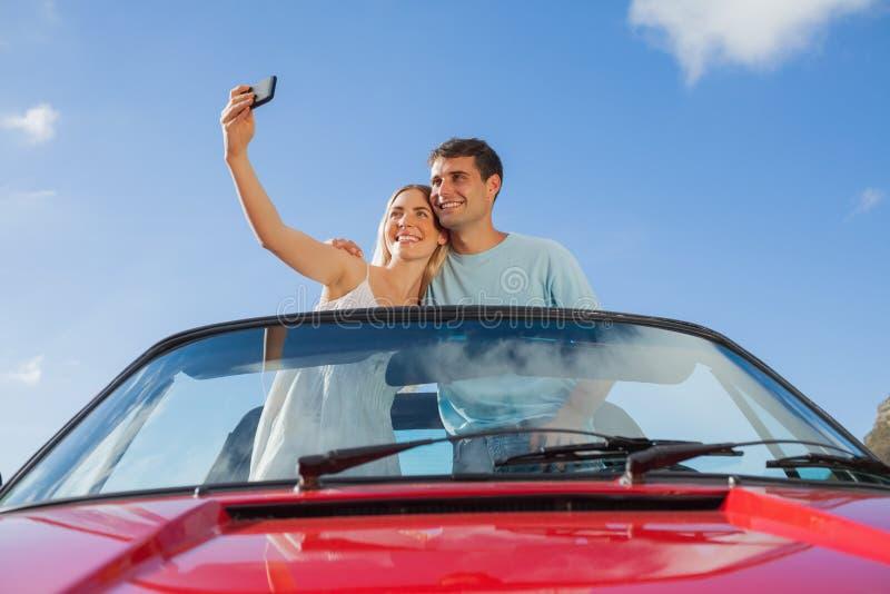 站立在红色敞蓬车的快乐的夫妇拍照片 免版税库存图片