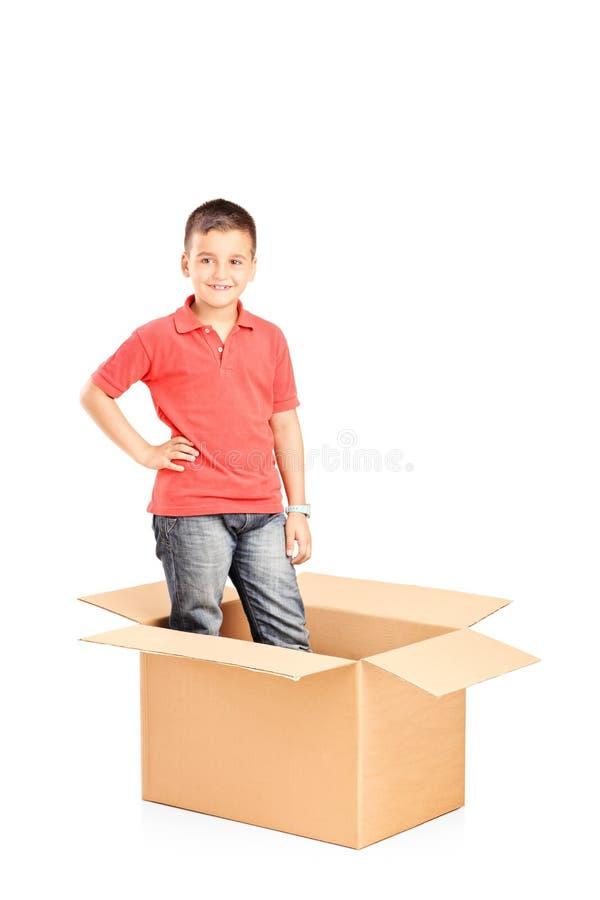 站立在纸盒箱子的小男孩 库存照片