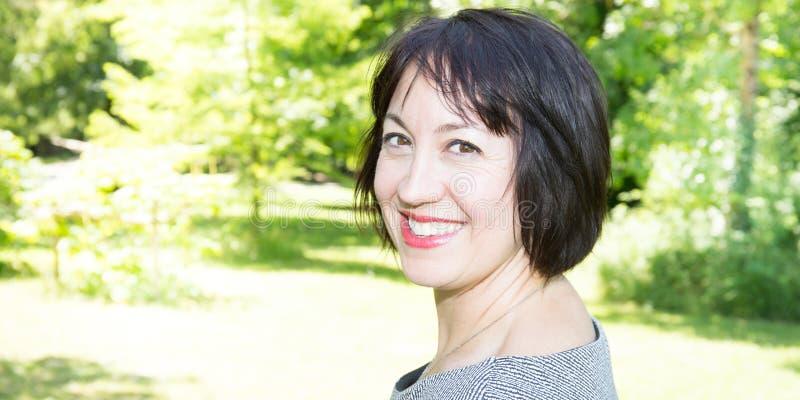 站立在绿色公园庭院的一名微笑的中间妇女的画象 库存图片