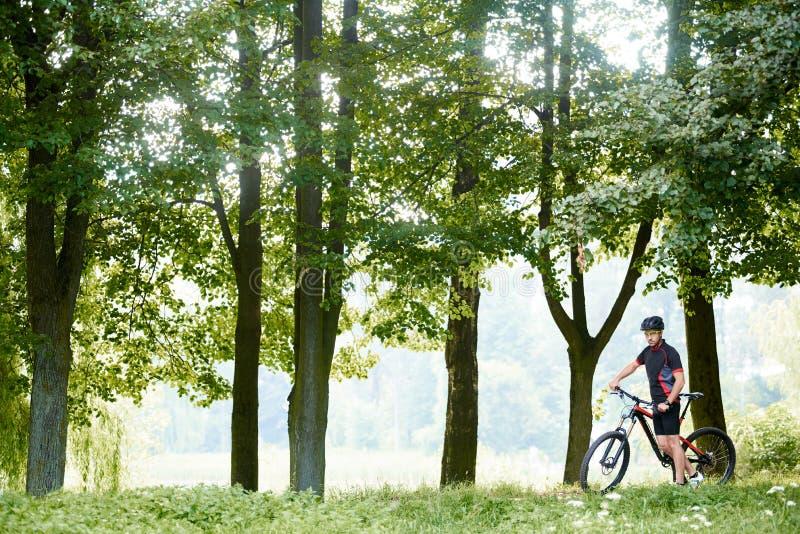 站立在绿色美丽的树中的骑自行车者近的自行车 免版税图库摄影