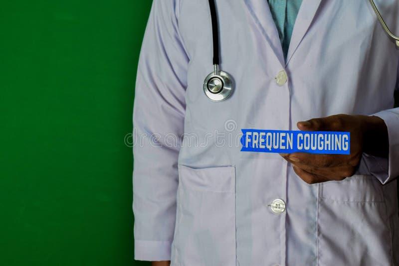 站立在绿色背景的医生 举行咳嗽纸文本的Frequen 图库摄影