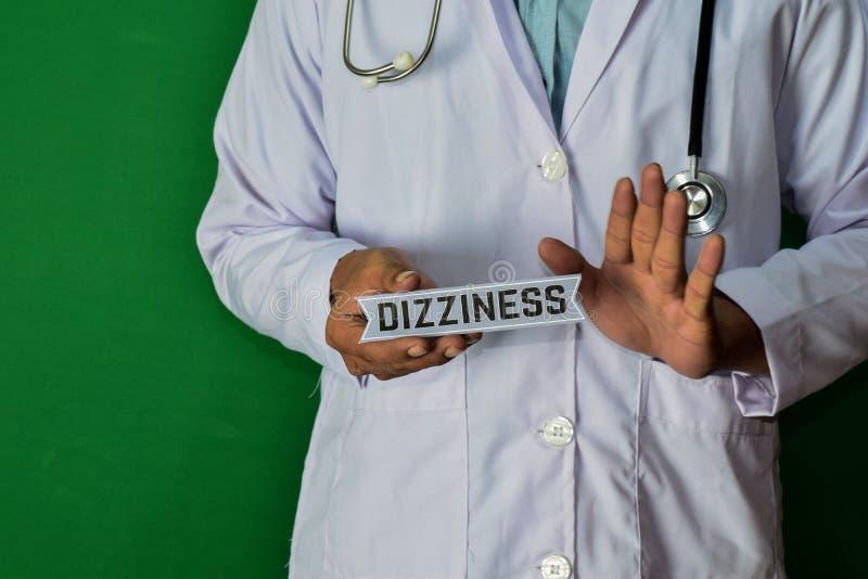站立在绿色背景的医生 拿着头晕纸文本 免版税库存照片