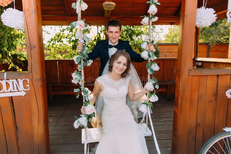 站立在美丽的新娘后的英俊的新郎画象坐摇摆 免版税库存图片