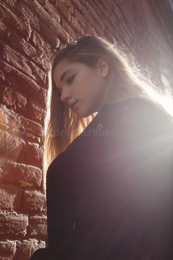 站立在美丽的日落背后照明的一个砖墙前面的黑色大衣的少女 寂寞的概念 免版税库存照片