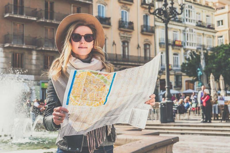 站立在美丽的欧洲城市街道上在喷泉附近和拿着目的地地图的帽子的少妇游人 库存照片