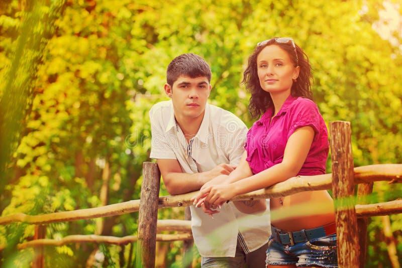 站立在老木桥和看照相机的年轻夫妇 库存照片