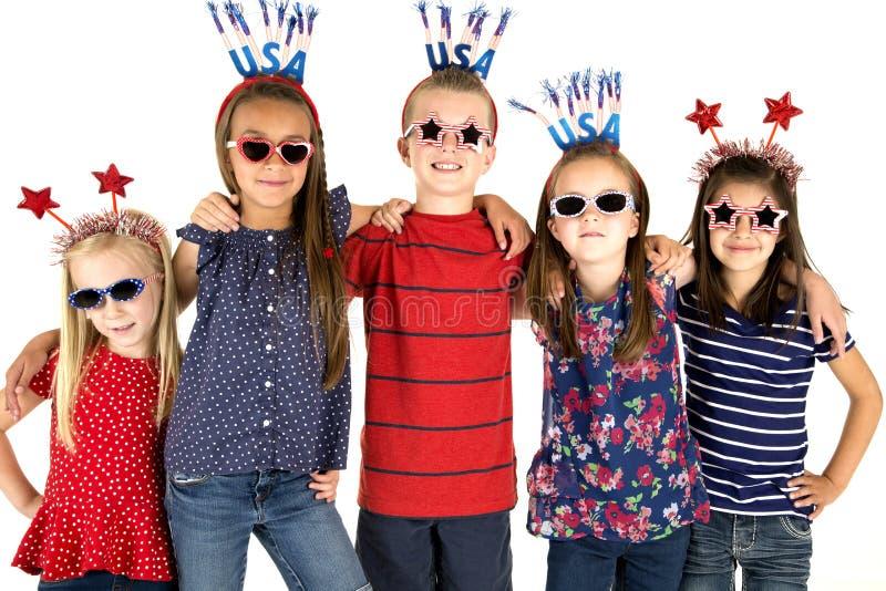 站立在胳膊微笑的五个爱国的孩子胳膊 免版税库存照片