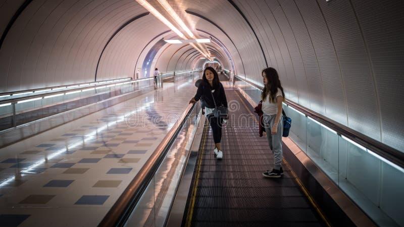 站立在自动扶梯的隧道的妇女 免版税图库摄影