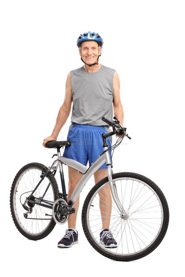 站立在自行车和微笑后的资深骑自行车的人 免版税库存图片
